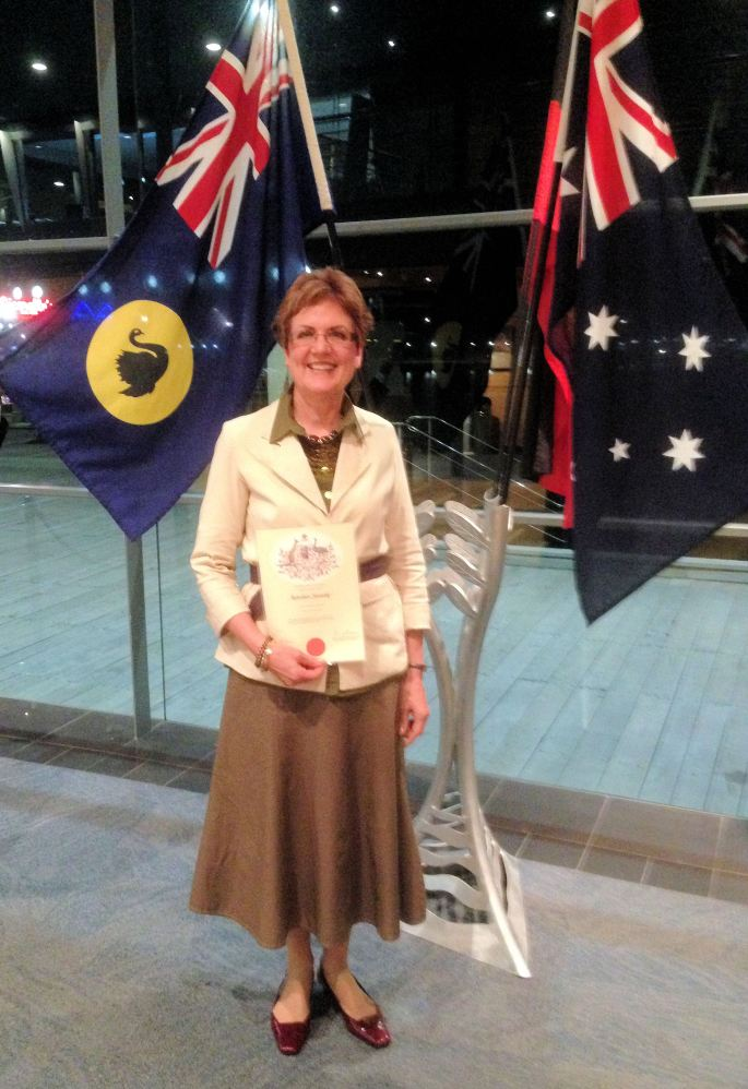 Karen holding Australian Citizenship Certificate with the flag of Western Australia on the left and the Commonweatlth Australia on the right